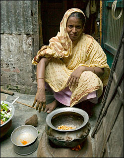 woman sitting next to cooking stove with pots of food