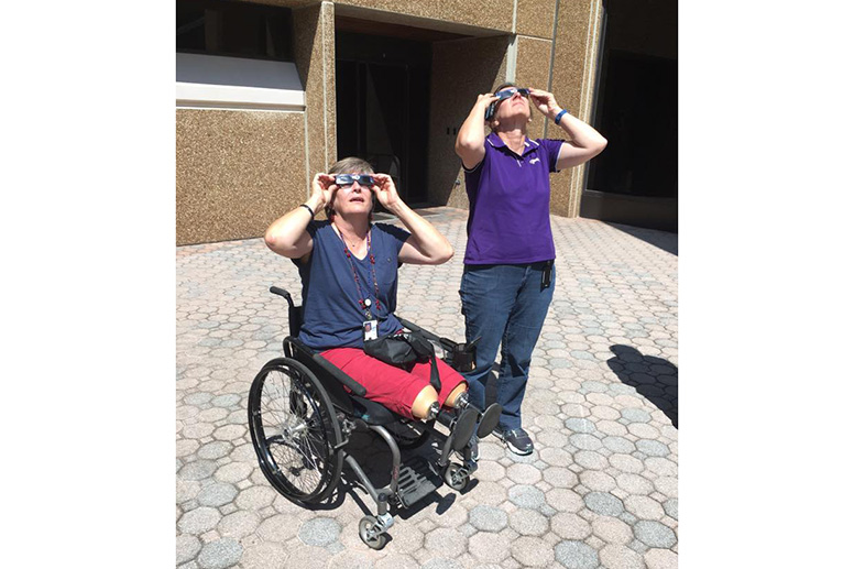 employees peer at the eclipse on campus